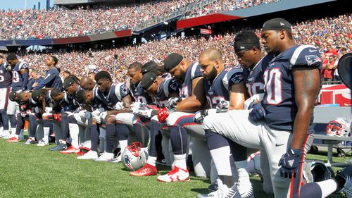 Members of the New England Patriots kneel on the sidelines as the National Anthem is played before a game against the Houston Texans at Gillette Stadium. (AFP)
