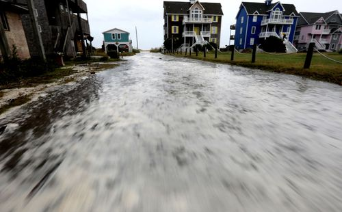 Ocean water rushes down a street on Hatteras Island as the effects of Hurricane Florence reach the coast of the Carolinas.