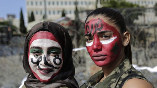 "Anti-government protesters with the colors of the Lebanese national flag painted on their faces and with Arabic that reads ""Revolution,"" pose for a photograph in front of the government palace in Beirut."