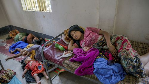 Rohingya women along with their children rest inside a health complex run by aid agencies in Kutupalong refugee camp, Bangladesh. (AAP)
