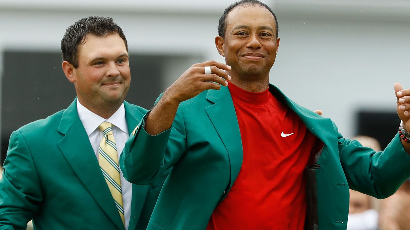 Patrick Reed, left, helps Tiger Woods with his green jacket after Woods won the 2019 Masters golf tournament