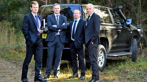 Detective Jubelin (far right) stands with other detectives while bushland is searched for signs of Tyrrell.
