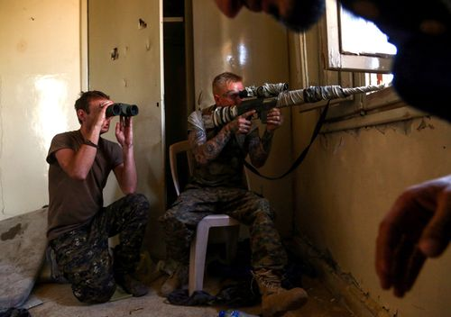 An American sniper (R) and British fighter supporting the Syriac Military Council in the fight against Islamic State guard a position in the suburb of al-Rumaniya on the western outskirts of Raqqa.
