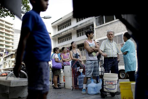 People in Venezuela are forced to line up to get water from limited trucks in Caracas, Venezuela.