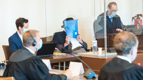 Bruno Dey, 93-year-old former SS security guard from the Stutthof concentration camp near Gdansk sits in a courtroom behind a plexiglass window next to his lawyer Stefan Waterkamp (R) and a doctor (L) in the regional court on July 23, 2020 in Hamburg, Germany