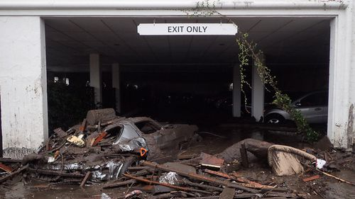 Damaged vehicles carried by mud flow and debris at the exit of the parking garage to The Montecito Inn. (AAP)