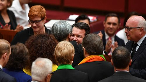 Penny Wong and Dean Smith embrace after the bill was passed 43-12. (AAP)