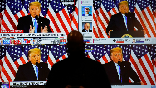 A live broadcast of President Donald Trump speaking from the White House is shown on screens at an election-night party, Tuesday, Nov. 3, 2020, in Las Vegas. (AP Photo/John Locher)