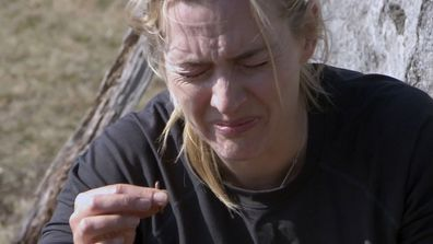 Katie Holmes tries a worm on Running Wild with Bear Grylls.