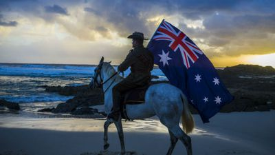 A member of the Light Horse Brigade carries the Australian flag at the dawn service held by the Currumbin RSL on the Gold Coast. (AAP)