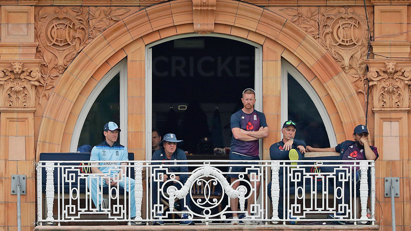 England's captain Eoin Morgan, left, sits on the players' balcony after getting out for four runs