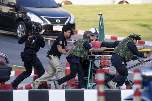 Armed commando soldiers carry a person out of Terminal 21 Korat mall