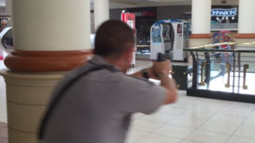 A police officer draws his gun inside the shopping centre. (Twitter: Tony Rice)