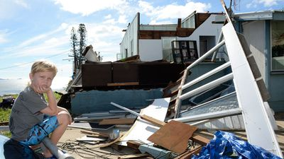 Tarn Smith, 7, is seen in front of his family's damaged home in John St, Yeppoon. (AAP)