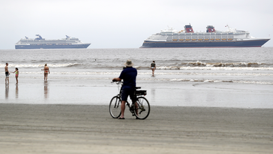 The Disney Wonder cruise ship, right, sits at anchor in front of Celebrity Cruise's Millennium cruise ship, as people pass on the beach Thursday, April 30, 2020, in Coronado, Calif.