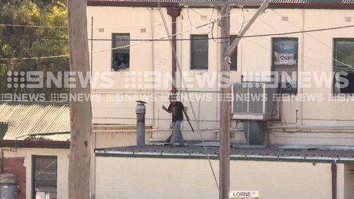 The man, who is armed with what apepars to be a machete, is refusing to come down from the roof of the local pub. (9NEWS)