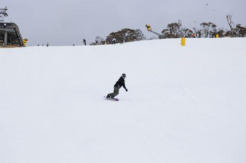 A snowboarder carves fresh snow on Perisher.