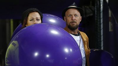 Grief-stricken parents of MH17 crash victims Evie, Mo and Otis Maslin prepare to release balloons before the Fremantle v Carlton AFL match. (AAP)