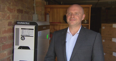 Chris Williams, CEO and Founder of Natural Solar - Australia's largest batter installer - stands in front of  Australia's first Duracell battery.