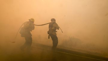 Firefighters battle a fire along the Ronald Reagan.