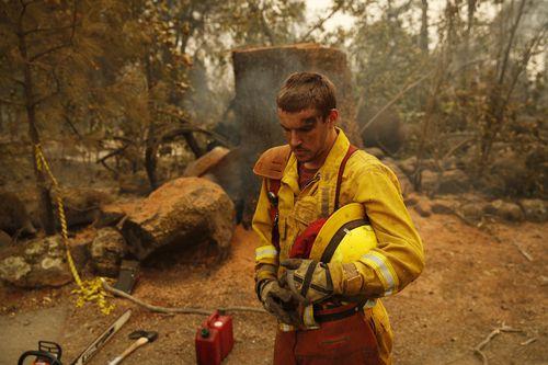Firefighter Shawn Slack rests after felling trees.