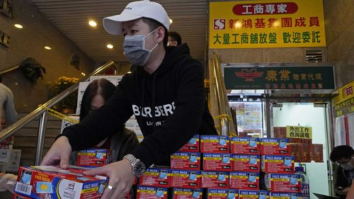 A Hong Kong shop worker puts face masks on display as the coronavirus spreads.