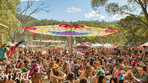 "Revellers sit under a shadecloth at NSW musci festival ""Pysfari""."