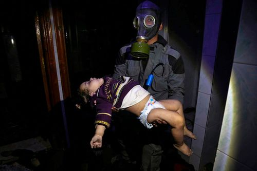 A rescue worker carries an injured child following the suspected chemical weapsons attack. (AP/AAP)