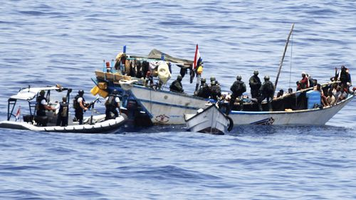 In this 2009 photo, Yemeni fishermen who are held hostage hold their hands up in the Gulf of Aden. Dutch marines boarded a fishing boat and freed two dozen Yemenis from the clutches of nine pirates. (AAP)