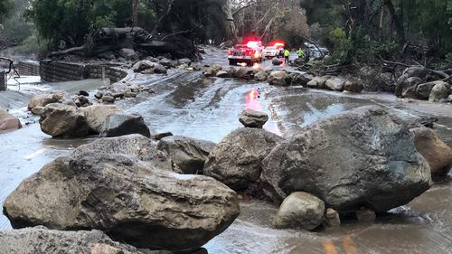 Santa Barbara County Firefighters work admist flood waters and debris flow during heavy rains in Montecito. (AAP)