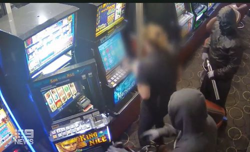 The armed men standing over the worker as she unlocks the gaming machines.