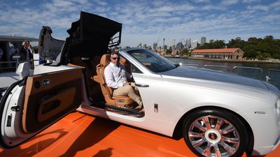 <p>The sleek new car has been described as the sexiest Rolls-Royce ever. Rolls Royce's Dawn Global Product Manager Jonathan Shears opens the roof and swings the door open to showcase the vehicle. (AAP)</p>