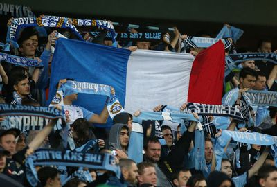 The French flag is held high in the crowd during an A-League in Sydney.