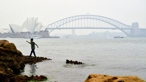 A young boy climbs on the rocks at Mrs Macquarie's Chair as smoke haze from bushfires in New South Wales blankets the CBD in Sydney