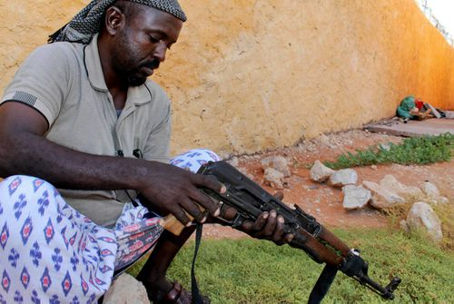 A Somali clansman cleans his AK-47 assault rifle.