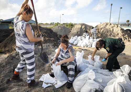 Female inmates from Brevard County Jail fill sandbags to hand out to residents in Cocoa, Florida