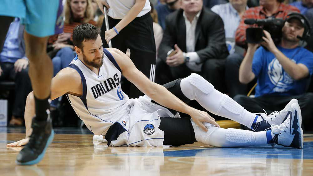 Andrew Bogut checks out his knee after falling in the NBA. (AAP)
