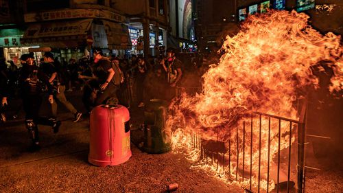 Pro-democracy protesters run behind a burning barricade after police charged toward them during a demonstration in Mongkok district on October 1, 2019 in Hong Kong.