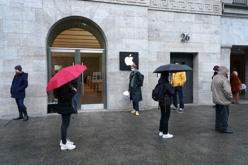 People stand in line and socially-distanced to enter the Berlin Apple store on the first day the store reopened since March
