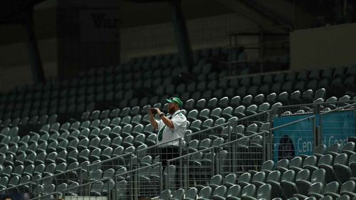 A security guard stands in an empty stadium in Gosford during an A-League game last month.