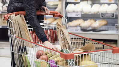 Woman filling trolley with groceries
