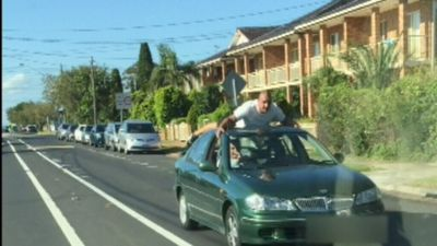 Reckless car surfer clings to roof of moving vehicle