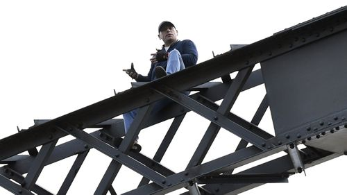 The man was sitting precariously on the bridge beams with police for around five hours. (AAP)