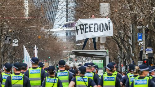"""A man holds a banner reading """"Freedom"""" atop a tram stop during an anti-lockdown protest in Melbourne on August 21, 2021. coronavirus"""