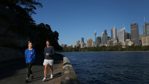 People are seen exercising along the Sydney Harbour shorefront
