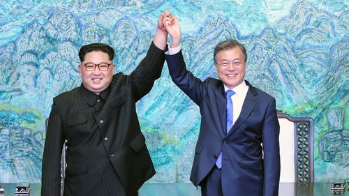 South Korean President Moon Jae In and North Korean leader Kim Jong-un raise their hands after signing a joint statement in 2018.. (AP)