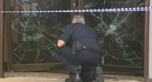A detective examines the damage at the scene of the ram-raid.