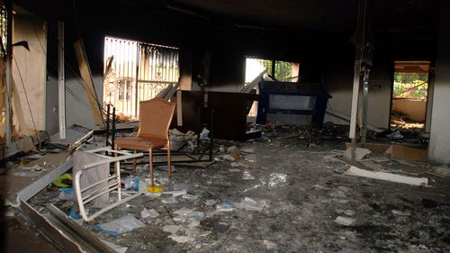 Glass, debris and overturned furniture are strewn inside a room in the gutted U.S. consulate. (AAP)