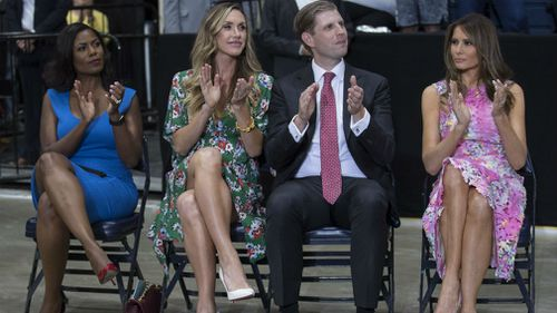 Omarosa Manigault, Eric Trump, the son of President Donald Trump and his wife Lara Trump and first lady Melania Trump sit to the side of the stage as President Donald Trump speaks during a Make America Great Again rally. (AAP)