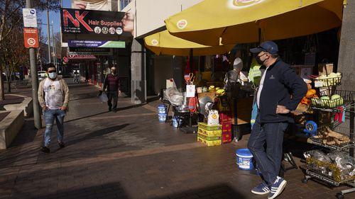 Shopkeeper Elias waits for customers in Fairfield, Sydney.